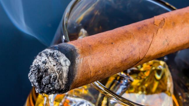 Zigarre und Whisky Whiskey Alkohol Symbolbild Sucht Genuss Blätter von Tabak und fertige Zigarren