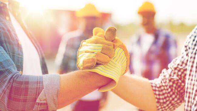 Bauen Bau Bauarbeiten Hausbau Teamwork Verhandlung Hand Handschlag Baubranche Symbolbild