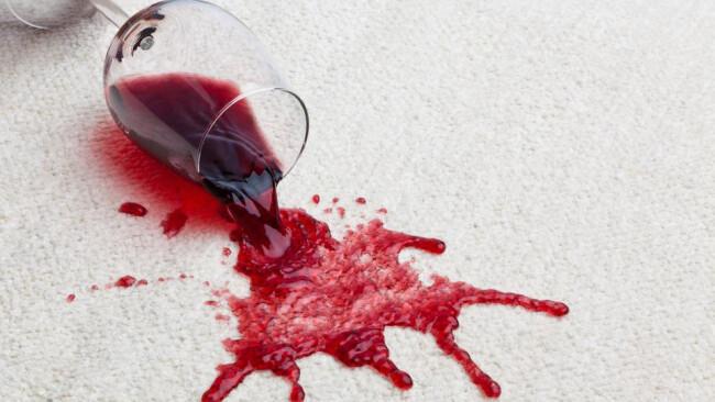 Wein Rotwein Uhudler Rotweinglas verschmutzt Teppich. Ein umgefallenes Glas mit Rotwein verschmutzt einen Teppichboden.