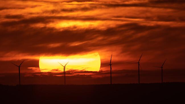 Sonnenaufgang über Windrädern