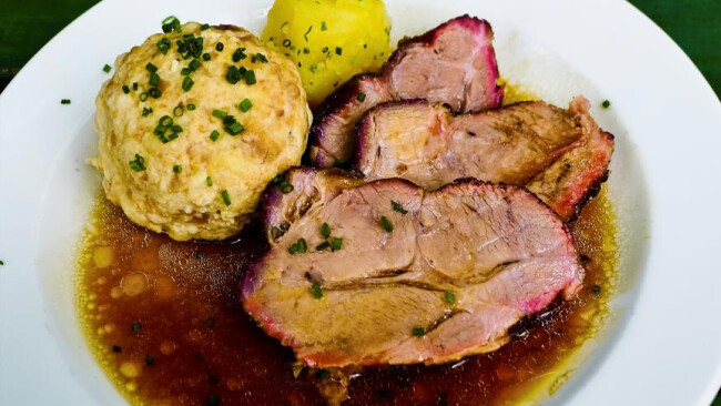 Schweinbraten auf einem Teller im Gasthaus Ein Schweinbraten wird auf einem Teller im Gasthaus serviert.