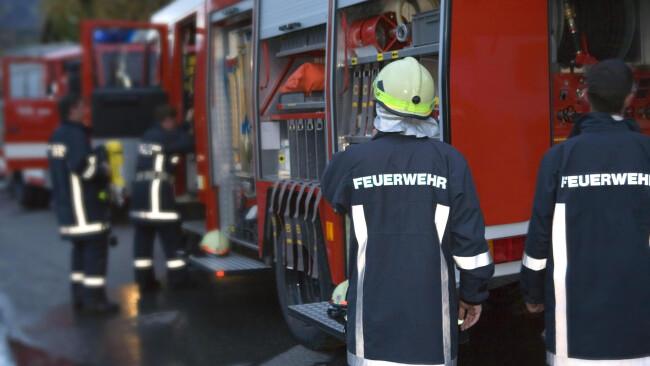 Feuerwehrleute vor einem Löschfahrzeug Widescreen