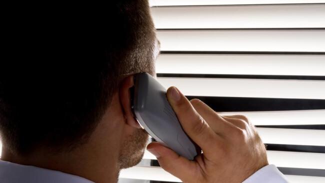 Neffentrick Telefon telefonieren Mann telefoniert Frau beobachtet etwas durch die Jalousie ihres Fensters