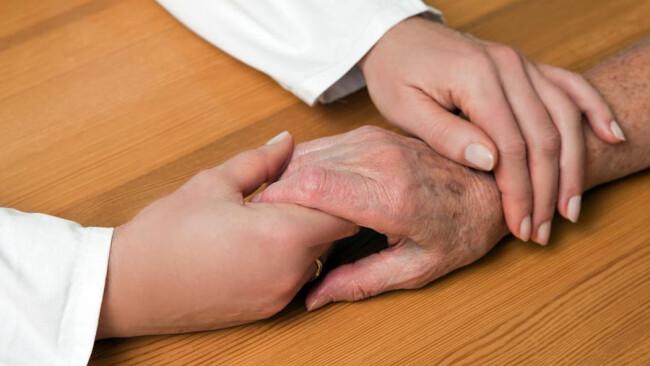 Hand einer Pflegerin und einer alten Seniorin Hände Pflegerin und einer alten Frau Pflege