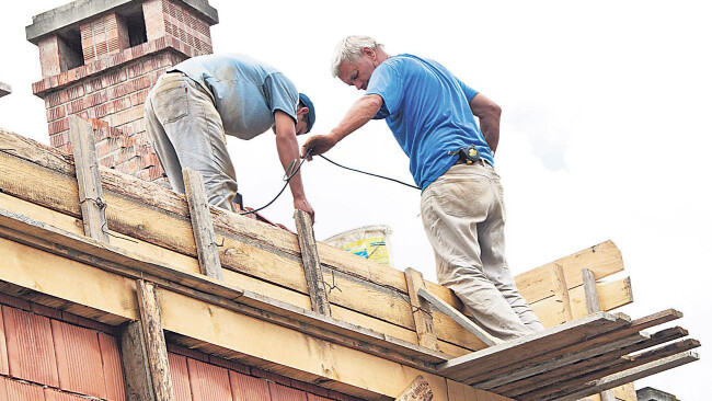 Bauarbeiter beim Dachdecken Symbolbild
